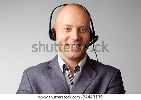 Portrait of a young handsome man with a headset on his head, who works in customer service - stock photo