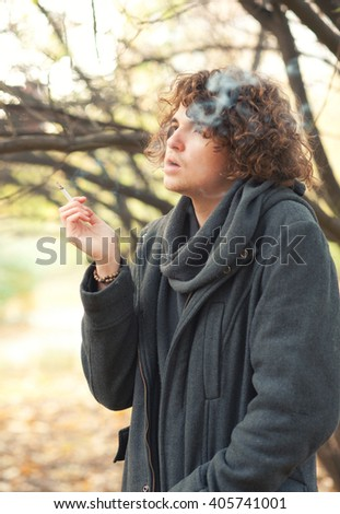 Portrait of a young handsome man with curly hairstyle dressed in gray jacket smoking a cigarette - stock photo