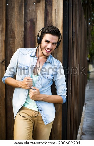 Portrait of a young handsome man with  headphones in urban background