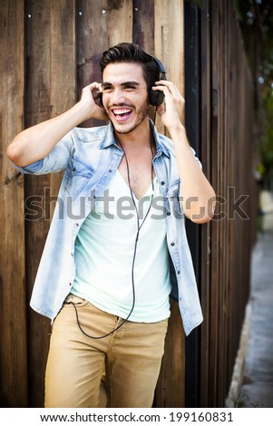 Portrait of a young handsome man with toupee and headphones in urban background - stock photo
