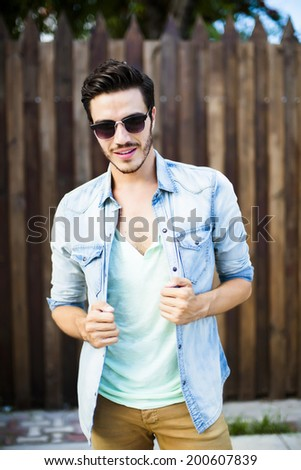 Portrait of a young handsome man with wooden background