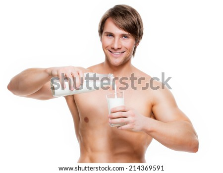 Portrait of a young handsome muscular man pouring milk into a glass - isolated on white background. - stock photo