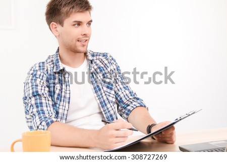 Portrait of a young handsome student sitting on the table holding a folder and a pen looking aside, thinking of new ideas for his project work, in a white room - stock photo