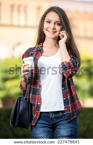 Portrait of a young handsome student with university building in the background. She is saying by phone. - stock photo