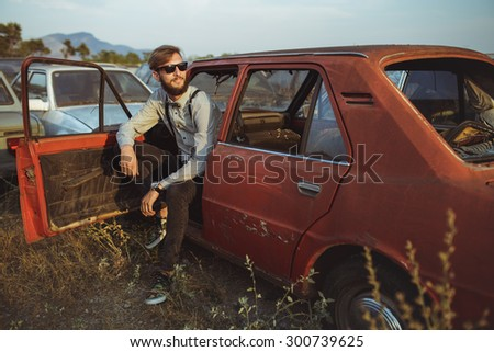 Portrait of a young handsome stylish man, wearing shirt and bow-tie with old cars - stock photo