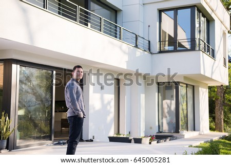 portrait of a young handsome successful man in front of his luxury home villa