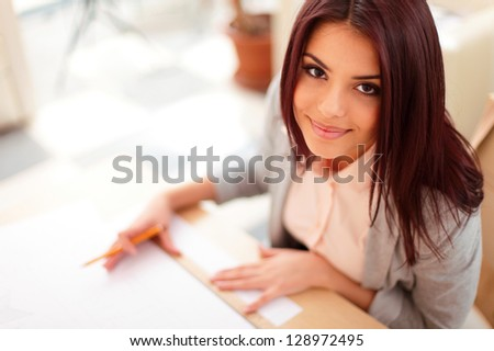 Portrait of a young happy beautiful architect working on blueprints - stock photo
