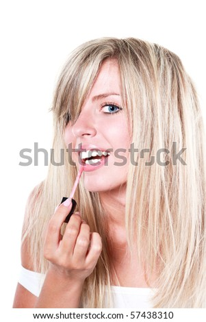 Portrait of a young happy beautiful woman applying lipstick isolated on white