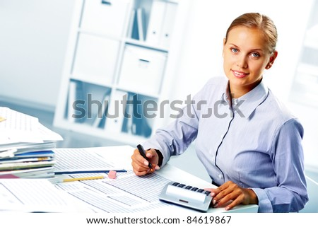 Portrait of a young happy businesswoman looking at camera while working in office - stock photo