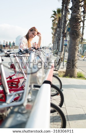 Portrait of a young happy charming hipster girl standing with bike on parking for bicycles with copy space area, attractive smiling woman cyclist posing on the street during walking in summer day - stock photo