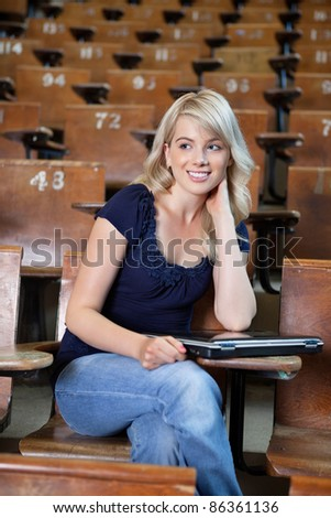 Portrait of a young happy college girl in lecture hall with a laptop - stock photo