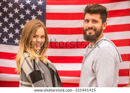 Portrait of a young happy couple on the background of the US flag - stock photo