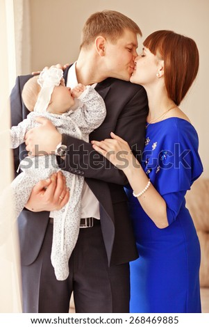 Portrait of a young happy family with the kid at home - stock photo