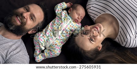 Portrait of a young happy family with the kid at home, top view - stock photo