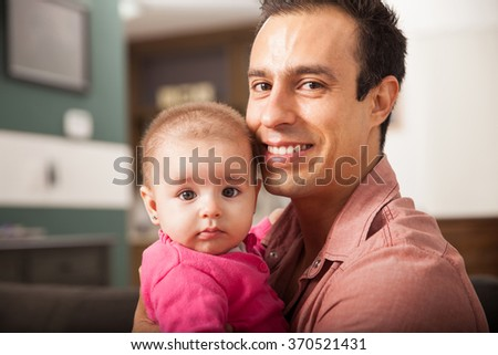 Portrait of a young happy Latin man spending time with his beautiful baby girl at home - stock photo