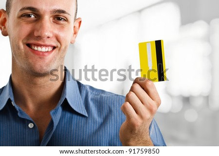 Portrait of a young happy man showing a credit card - stock photo