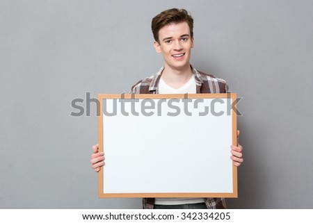 Portrait of a young happy man showing blank board over gray background - stock photo