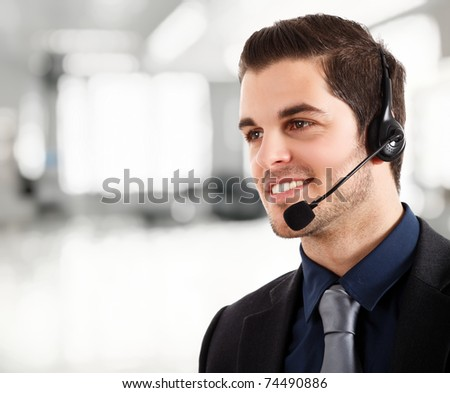 Portrait of a young happy phone operator. Bright blurred background.