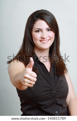 Portrait of a young happy woman gesturing ok over grey background - stock photo