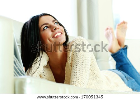 Portrait of a young happy woman lying and looking up at home - stock photo