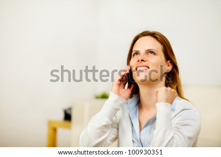 Portrait of a young happy woman on mobile phone while is celebrating be the winner while looking up - stock photo