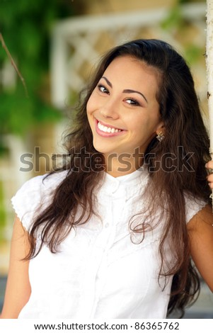 Portrait of a young happy woman smiling outdoors