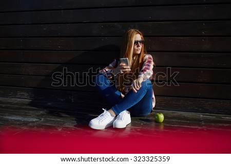 Portrait of a young hipster girl dressed in stylish clothes holding mobile phone while resting after walking in summer day, female student using cell telephone while resting on campus after lectures  - stock photo