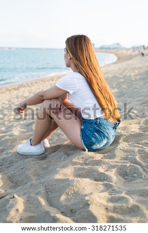 Portrait of a young hipster girl with long luxury hair enjoying beautiful nature landscape while sitting near the sea in summer day, pretty woman dreams while sitting alone on the beach relaxing - stock photo