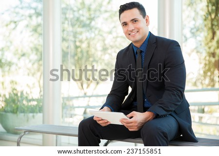 Portrait of a young Hispanic businessman using a tablet computer for work and smiling - stock photo