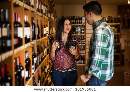 Portrait of a young Hispanic couple buying some wine bottles in a supermarket - stock photo