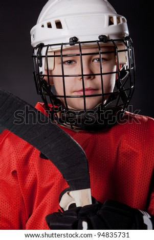 Portrait of a young ice hockey player in uniform on dark background - stock photo