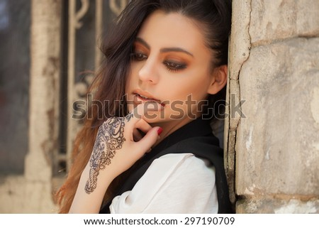 Portrait of a young indian woman in casual style with mehendi on the streets of old city - stock photo