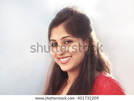 Portrait of a young Indian woman smiling, looking at the camera. Head shot.