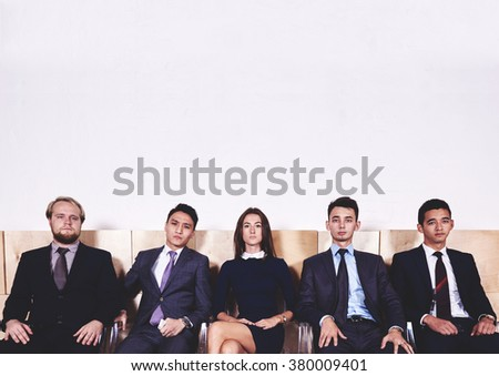 Portrait of a young international business people dressed in corporate clothes waiting for the conference, confident workers in formal wear ready to meeting with partners, copy space for text message  - stock photo