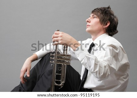 Portrait of a young jazz man and his Trumpet grey background - stock photo