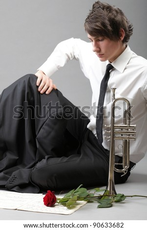 Portrait of a young jazz man andTrumpet grey background. Love melody - stock photo