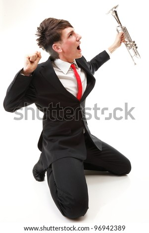 Portrait of a young jazz man joy, glee and his Trumpet white background - stock photo