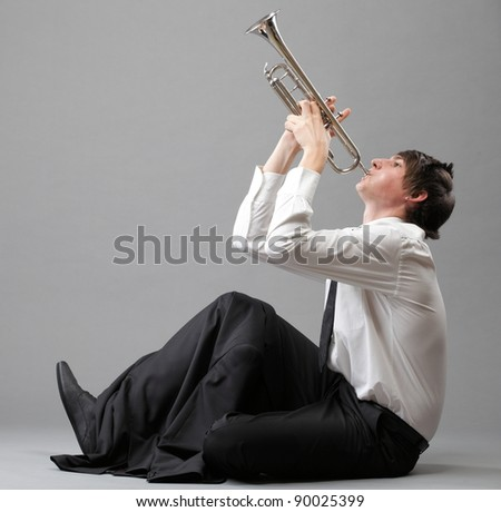 Portrait of a young jazz man playing his Trumpet grey background - stock photo