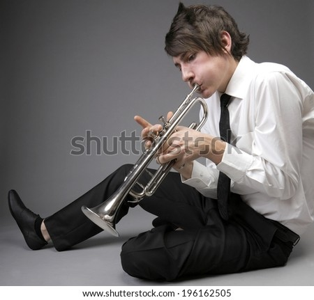 Portrait of a young jazz man playing his Trumpet grey background. Love melody - stock photo