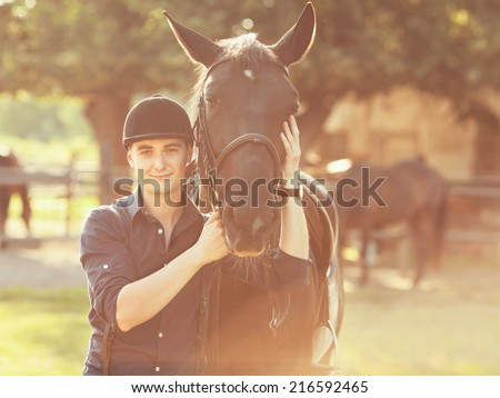 Portrait of a young jockey and his horse - stock photo