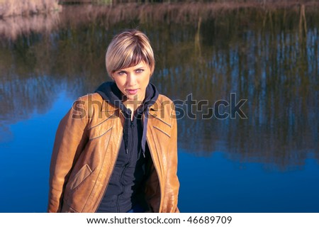 Portrait of a young lady in a park, in front of water reflecting trees. - stock photo