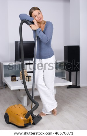 Portrait of a young lady in cleaning a living room floor - stock photo