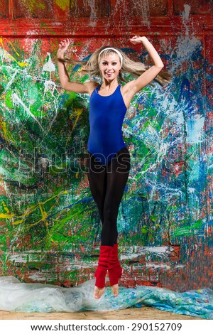 Portrait of a young lady, jumping in front of bright colored wall - stock photo