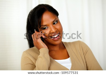 Portrait of a young lady looking down while talking on cellphone at home - stock photo