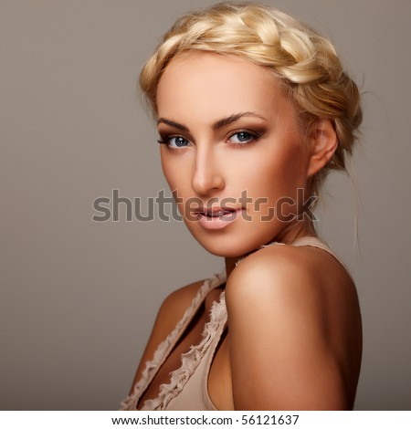Portrait of a young lady with a braid on grey background - stock photo