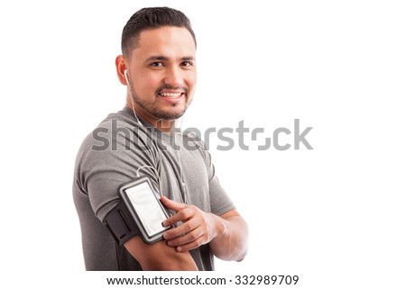 Portrait of a young Latin athlete wearing an armband and selecting his favorite song and playlist on a white background