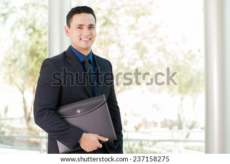 Portrait of a young Latin businessman carrying a portfolio at work - stock photo