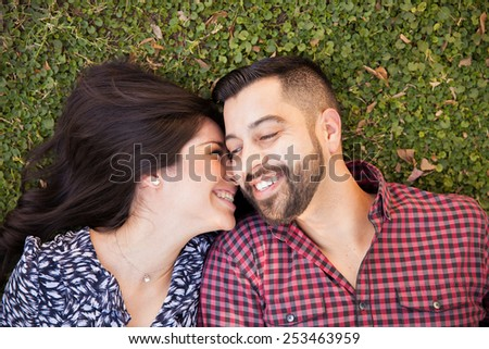 Portrait of a young Latin couple hanging out and relaxing at a park - stock photo