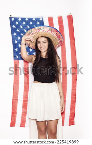 Portrait of a young Latina woman in sombrero on the background of the American flag. Portrait of girl on white background, not isolated