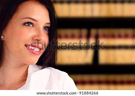 Portrait of a young lawyer standing in front of a bookcase - stock photo